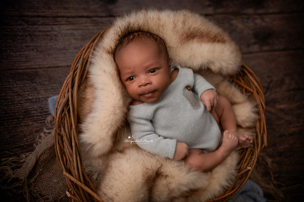 newborn with big brown eyes wearing a baby blue romper lying in basket stuffed with a brown fur blanket for his newborn photography session in aldershot hampshire berkshire surrey