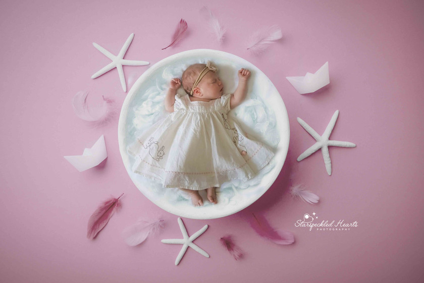 sleeping baby girl with arms stretched over her head, wearing a gorgeous white dress, laying in a basket surrounded by star fish and feathers