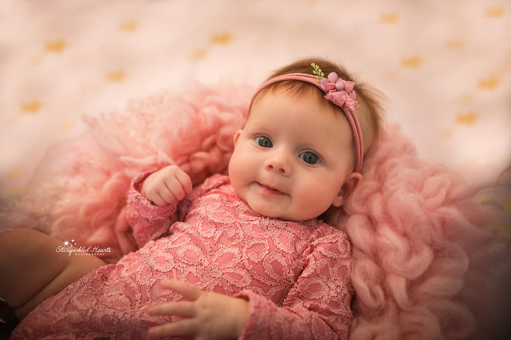 smiling baby girl wearing a pink lacy romper, lying on a bed of pink fluffy blankets on top of a pink blanket with gold stars