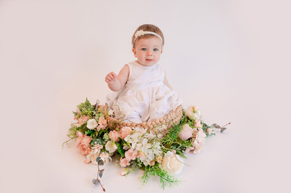 cute baby girl wearing a white dress sitting in a basket surrounded by florals for her baby photography session with starspeckled hearts photography