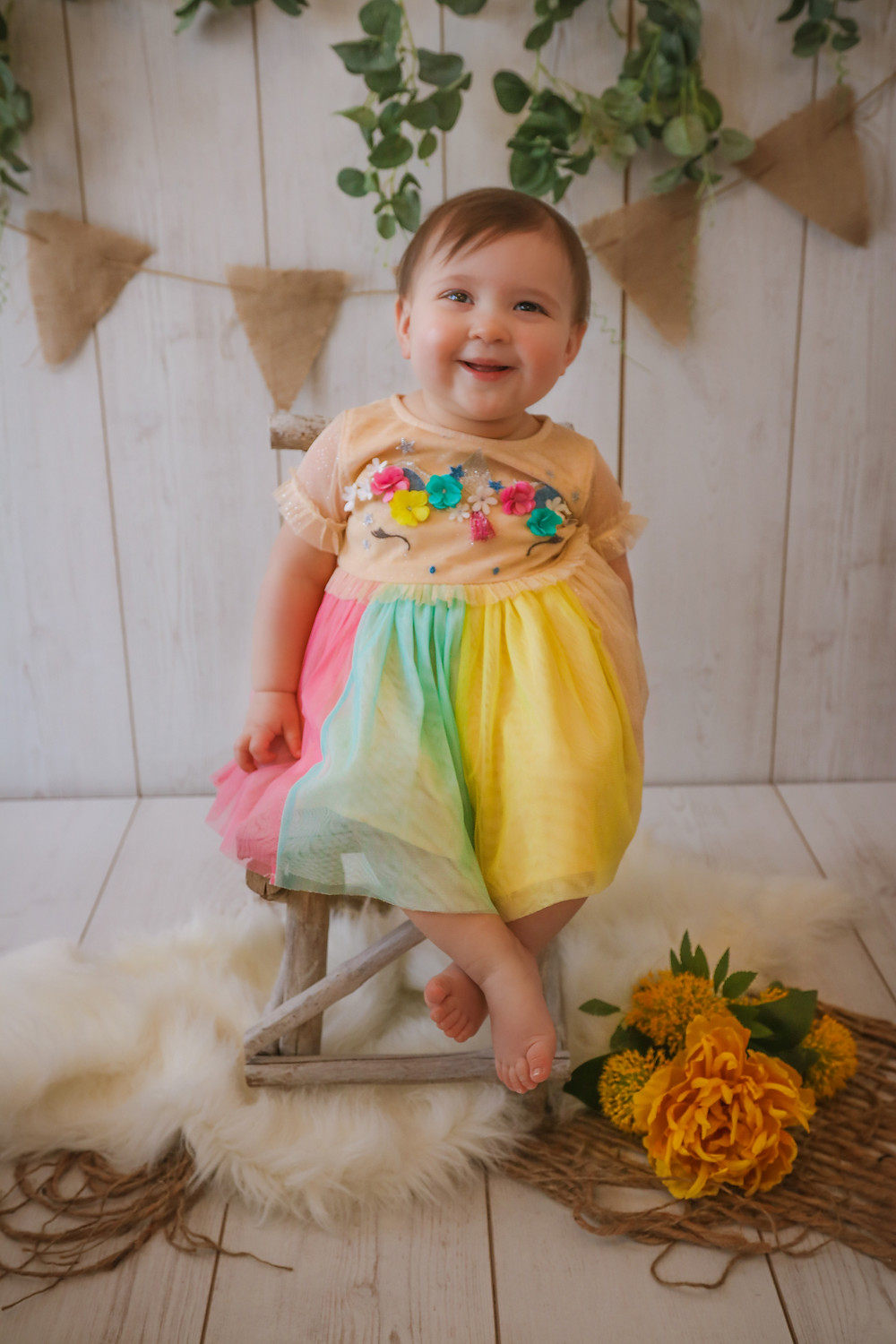 little girl sitting on chair smiling wearing a rainbow dress