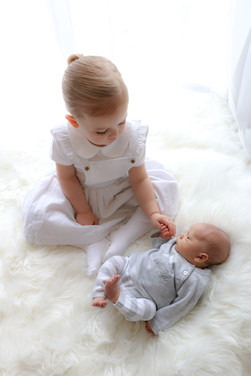 blonde toddler girl wearing overall dress sitting down next to her newborn brother, holding his hand