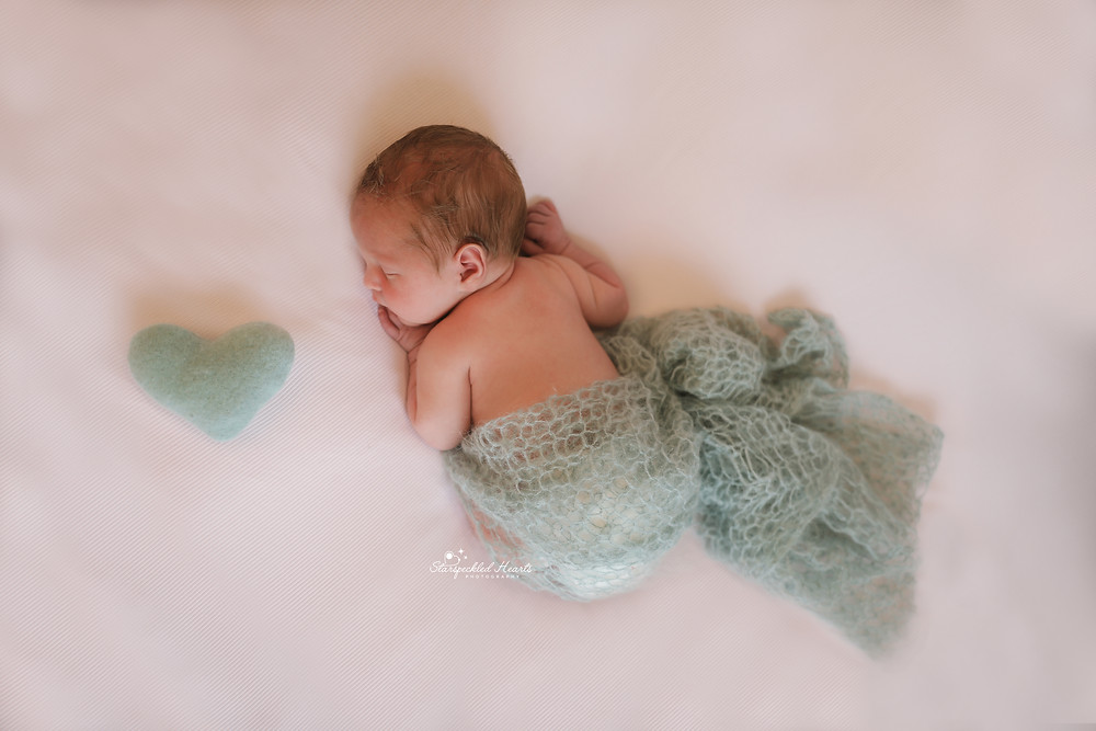 newborn laying on his front, with a duck egg blue wrap around his nappy