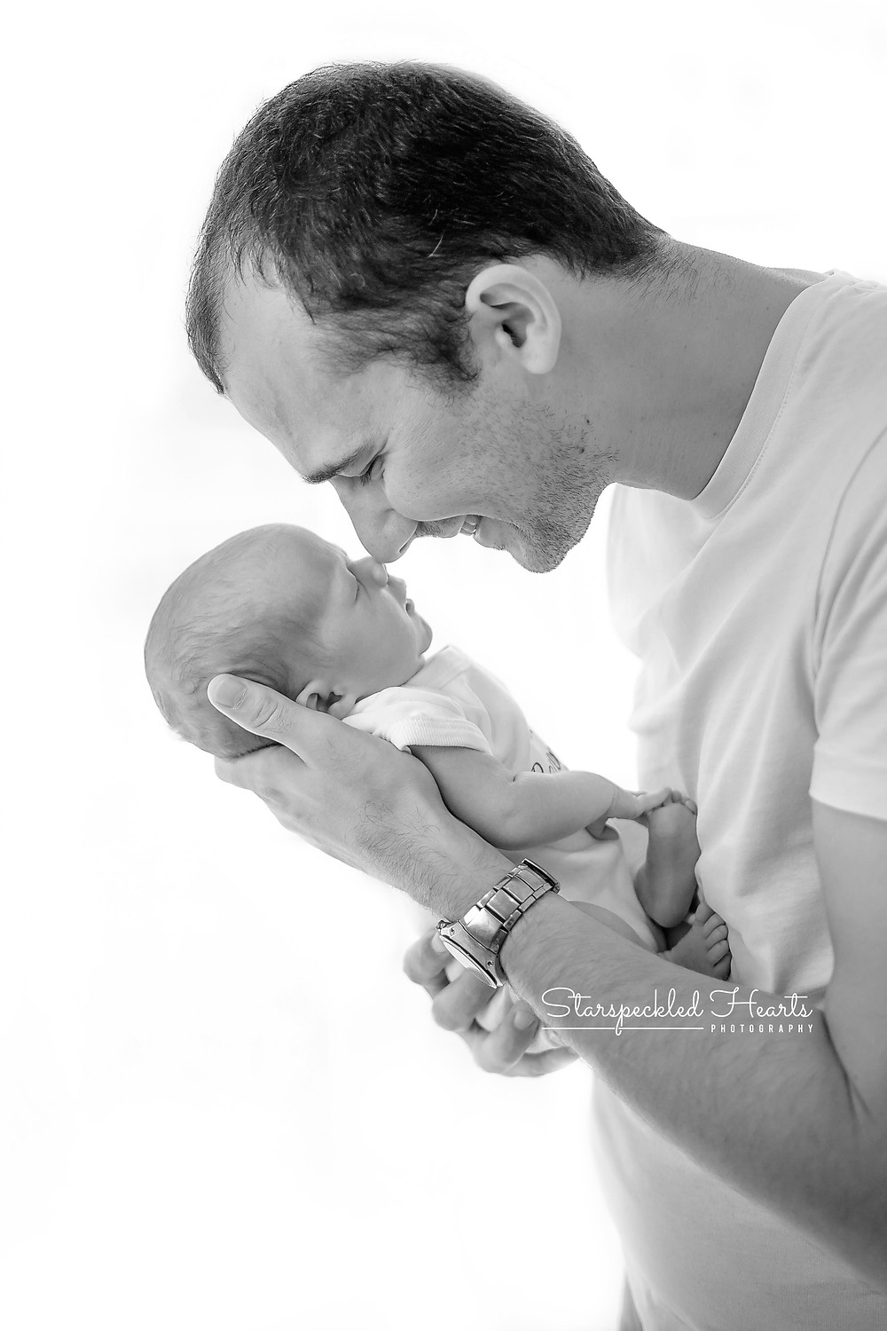 profile shot of a dad holding his newborn son up to his nose, smiling