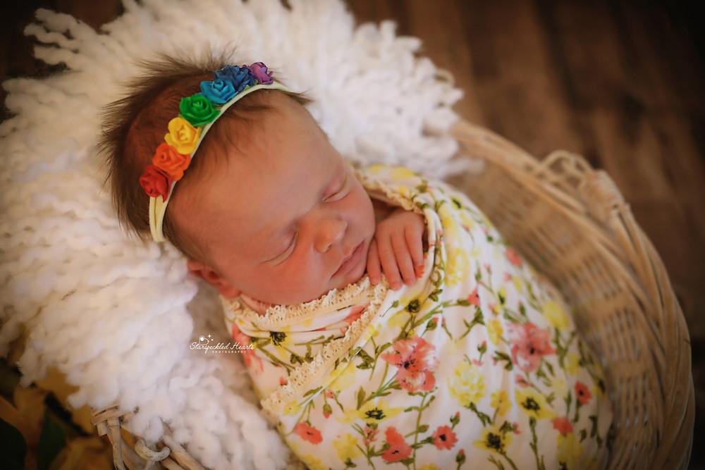 baby girl wearing a rainbow headband lying in a wicker basket on a dark wooden floor