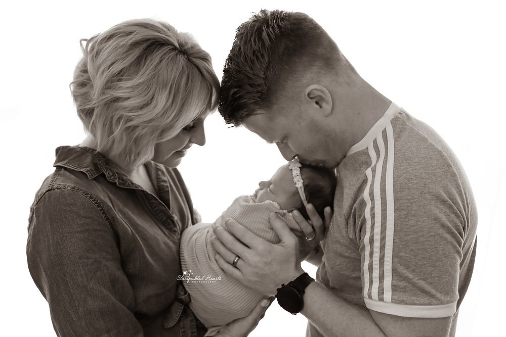 a man and woman holding their newborn baby