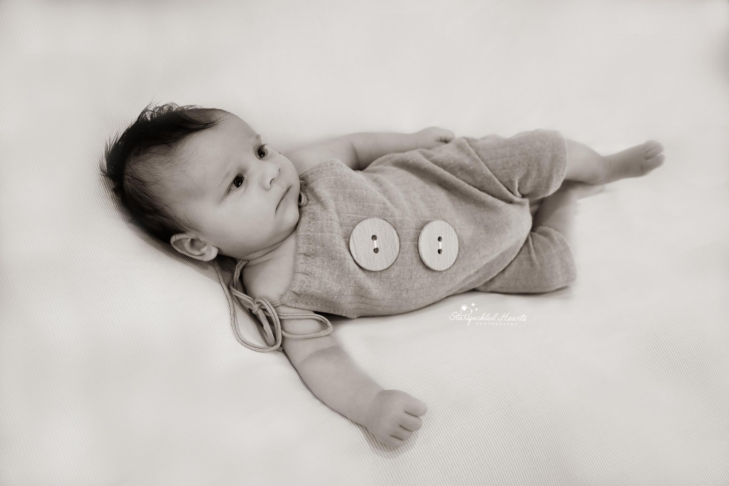 cute baby boy lying on a white blanket