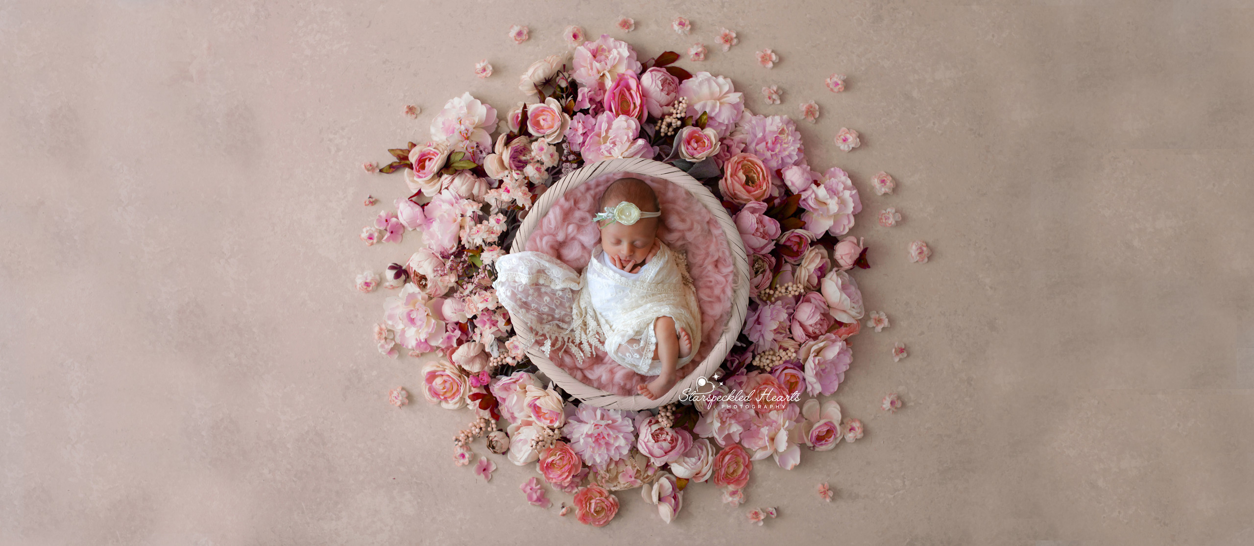 beautiful newborn girl lying in a bowl surrounded by pink roses and flowers