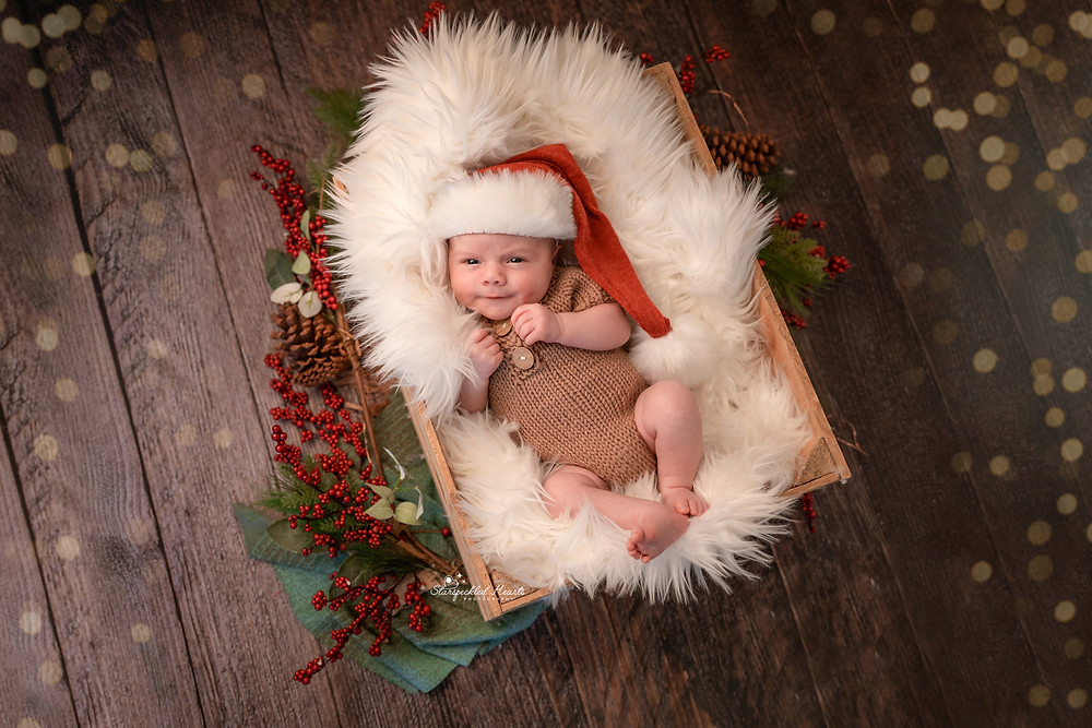 newborn wearing a santa hat lying in a wooden crate surrounded by fairy lights and christmas decor for his newborn photography session with starspeckled hearts photography