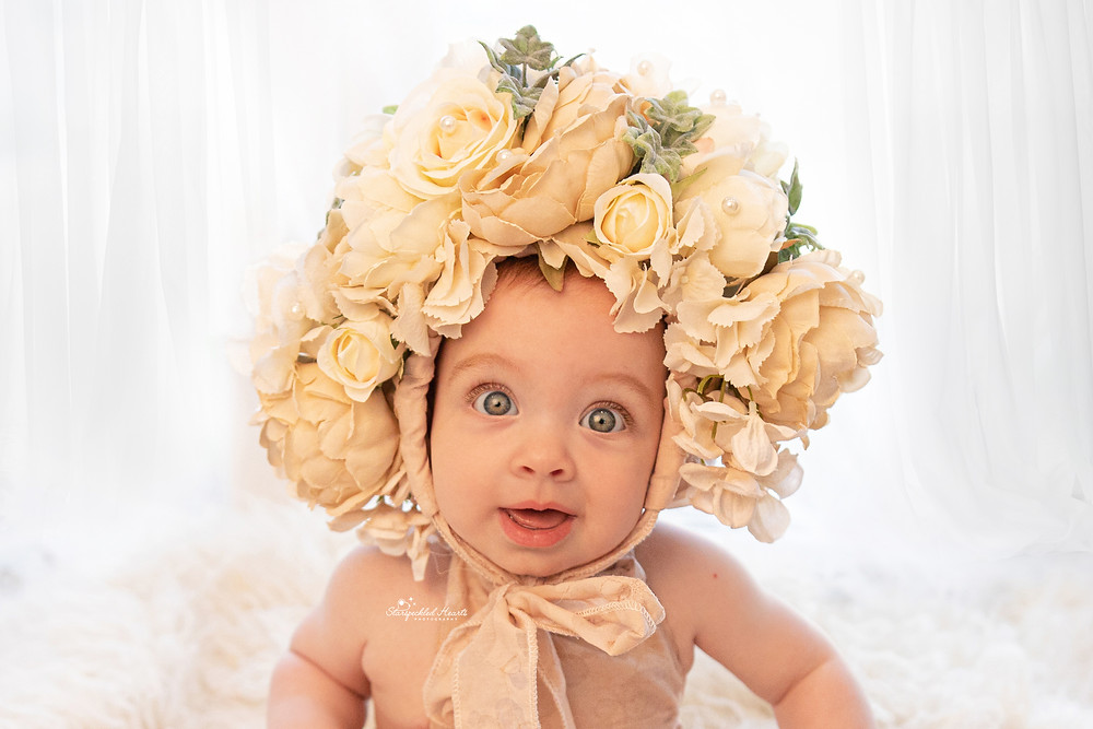 gorgeous baby girl wearing a flower bonnet with big blue eyes