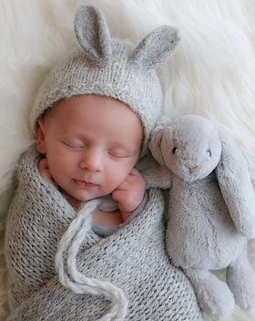 gorgeous sleeping newborn boy wearing a grey bunny bonnet, cuddling with a grey bunny teddy
