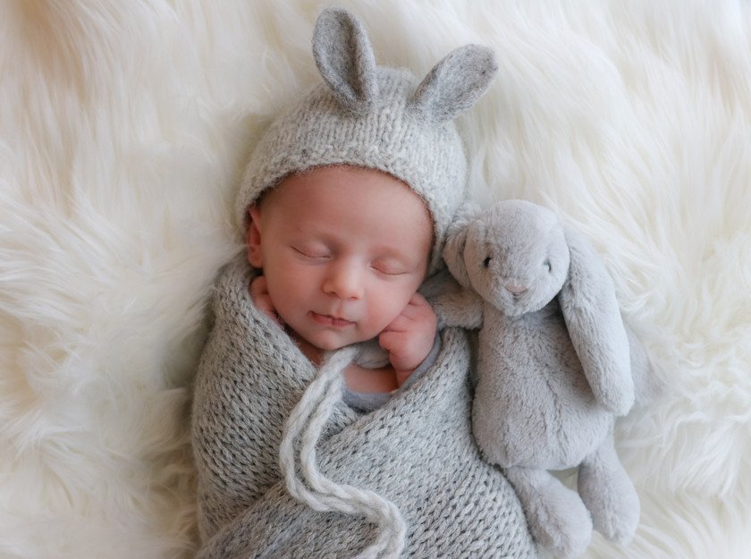sleeping newborn wearing bunny bonnet cuddling with bunny teddy