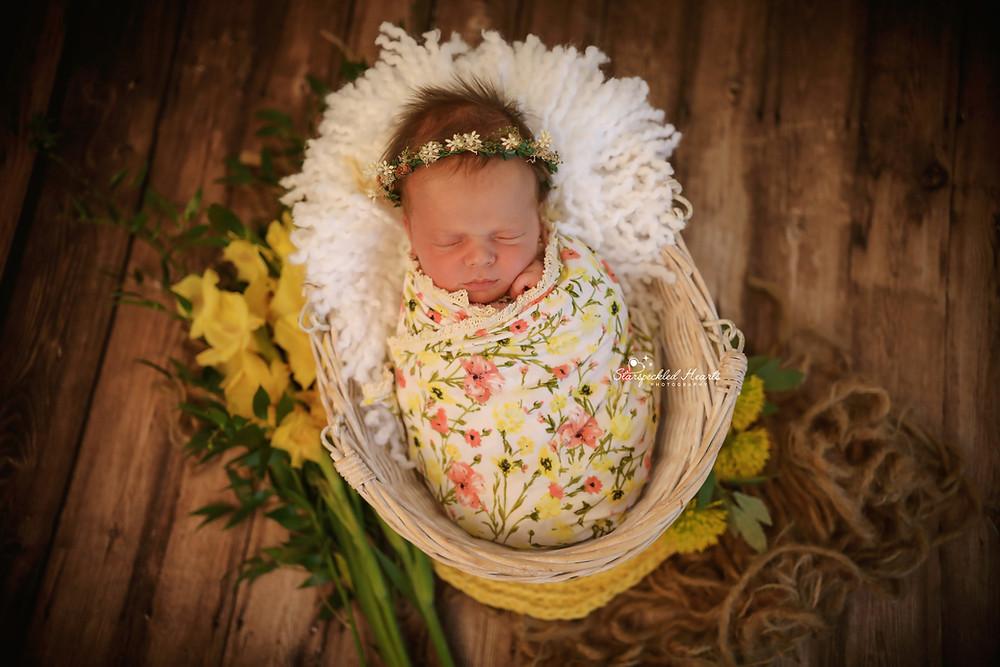 baby girl wearing a floral wreath lying in a wicker basket on a dark wooden floor