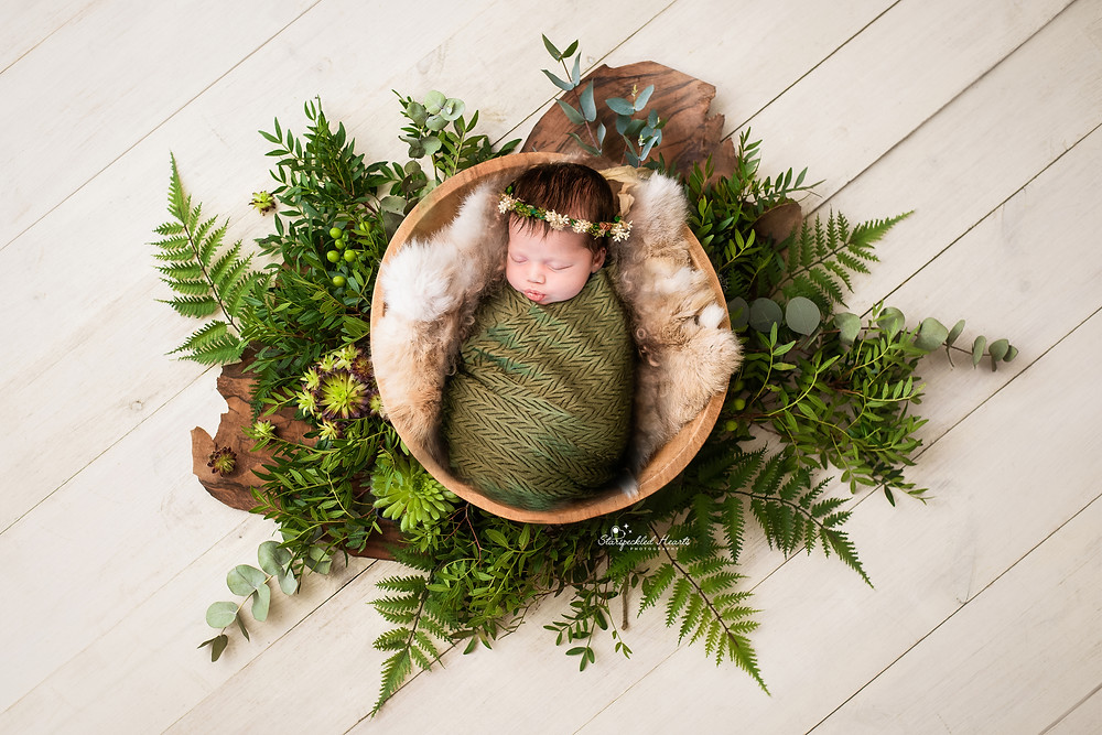 gorgeous sleeping newborn baby girl in a basket surrounded by greenery