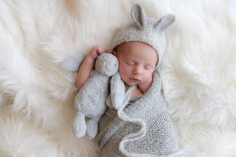 sleeping newborn wearing a grey bunny bonnet and matching grey wrap, cuddling a bunny teddy