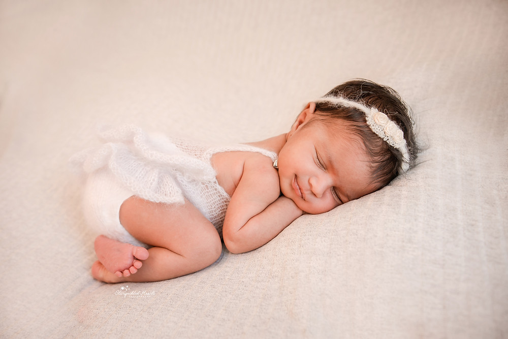 newborn lying on tummy on a grey backdrop at her newborn photography session with starspeckled hearts photography