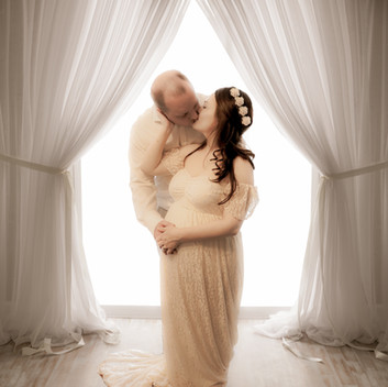 pregnant woman wearing a white lacey flowy gown and a floral headband kissing her husband in front of a large full height window with white sheer curtains