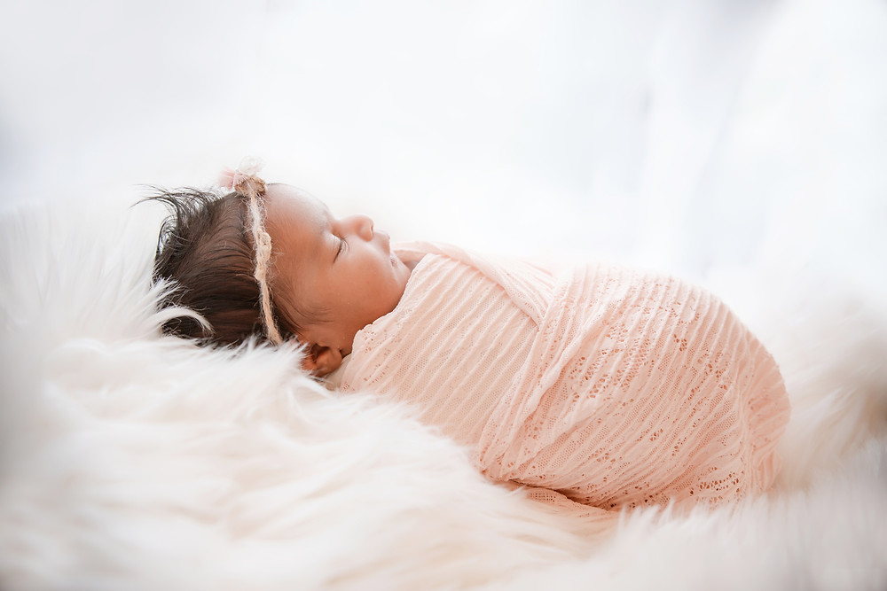 sleeping newborn baby girl swaddled in pink for her newborn photography session in hampshire
