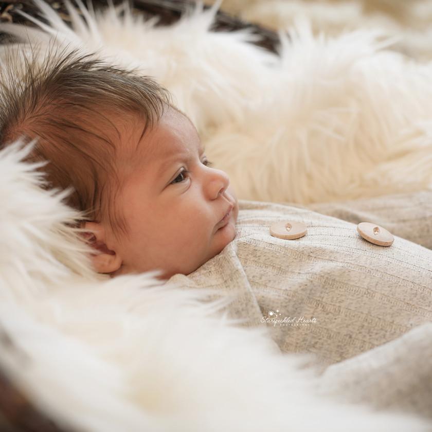 baby boy lying on a white fluffy rug