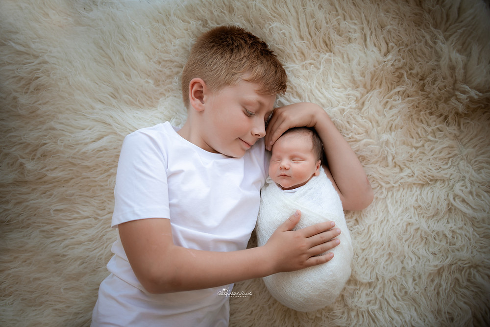 a swaddled newborn and his older brother lying down on a white rug together