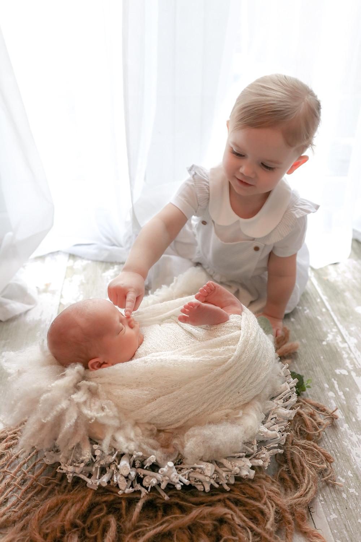 toddler girl poking newborn baby's nose