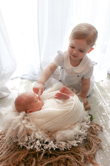 blonde toddler girl sitting up touching her newborn brothers nose, newborn laying down in a twig basket wrapped in a white textured swaddle