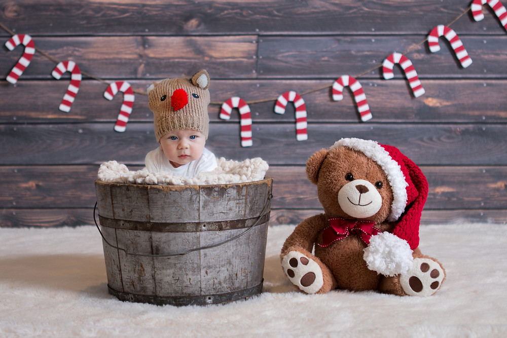 cute baby boy with a reindeer hat sitting in a wooden barrel with a large teddy on his right with a santa hat on