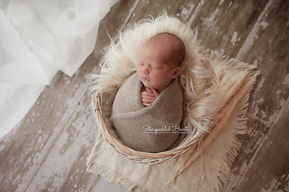 sleeping newborn swaddled in a brown knitted wrap for his newborn photoshoot in aldershot