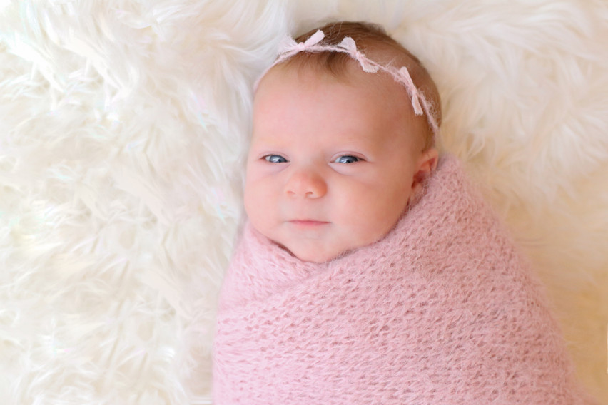 smiling newborn girl wrapped in pink wool
