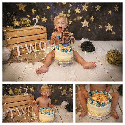 gorgeous baby boy with blonde hair having a space themed cake smash