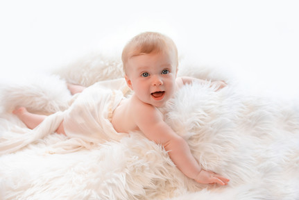 smiling baby girl lying on a white fluffy rug with a lacy wrap around her