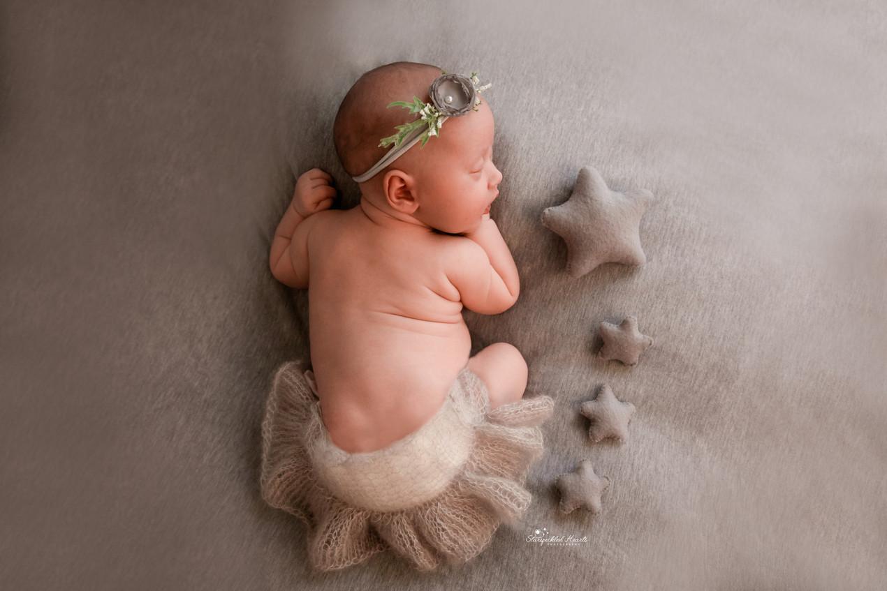 sleeping newborn baby girl lying on a grey backdrop wearing a grey headband