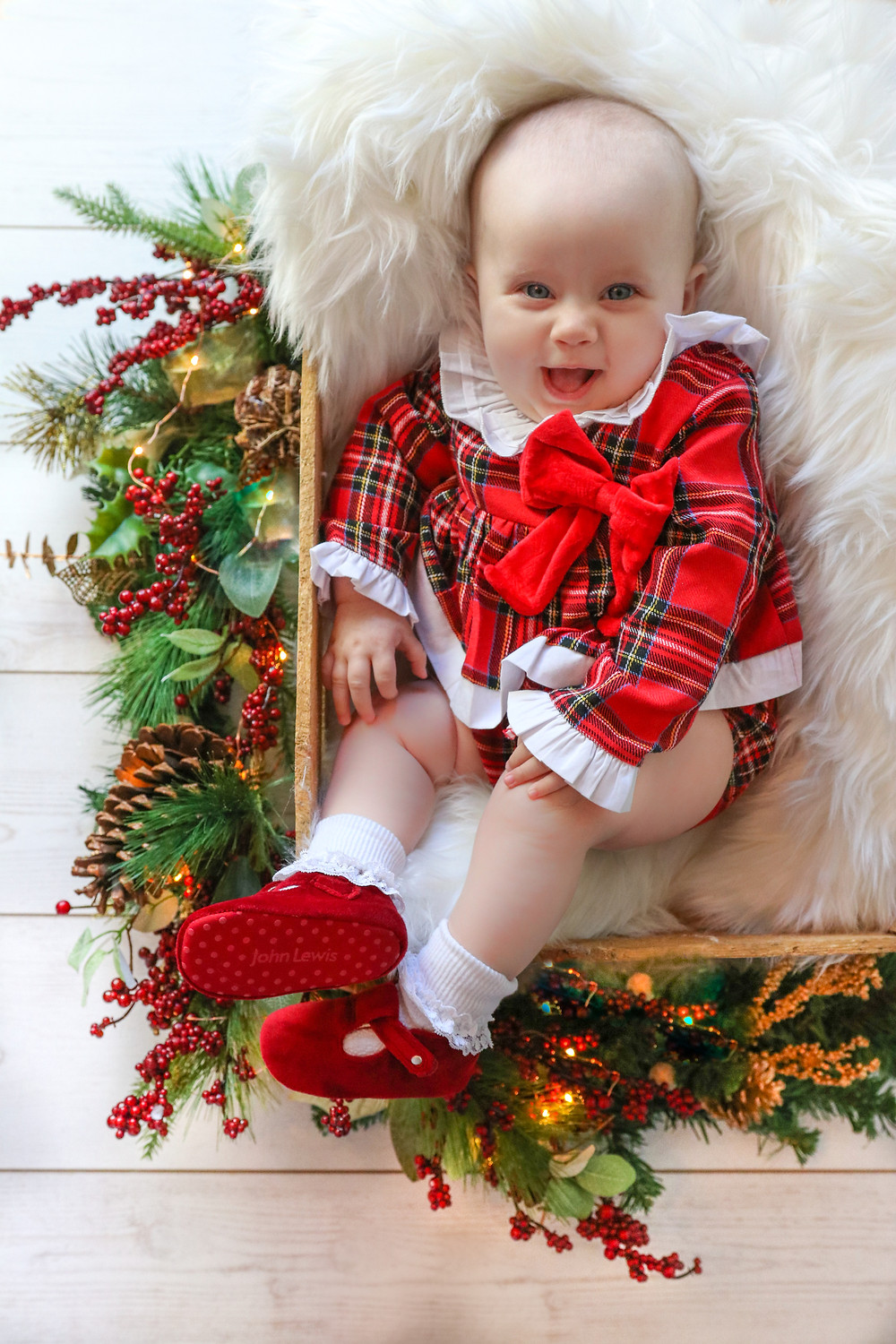 beautiful little baby girl wearing a red tartan outfit with a big red bow and matching red shoes, lying in a brown wooden crate stuffed with a white furry rug, surrounded by christmas decorations