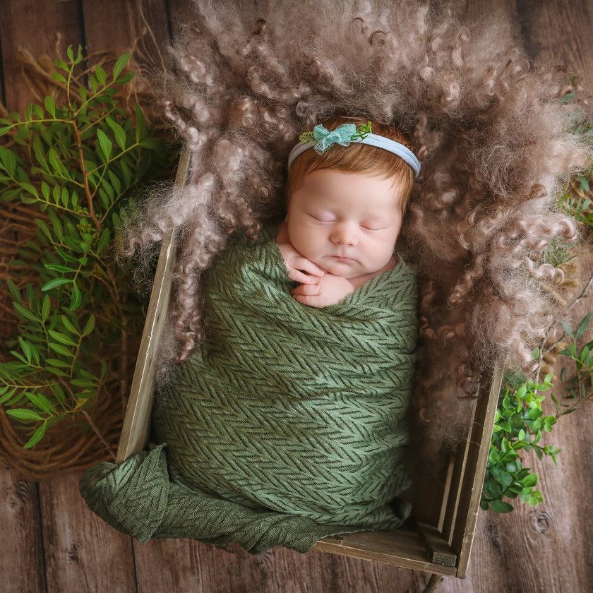 sleeping newborn girl in dark green wearing green headband