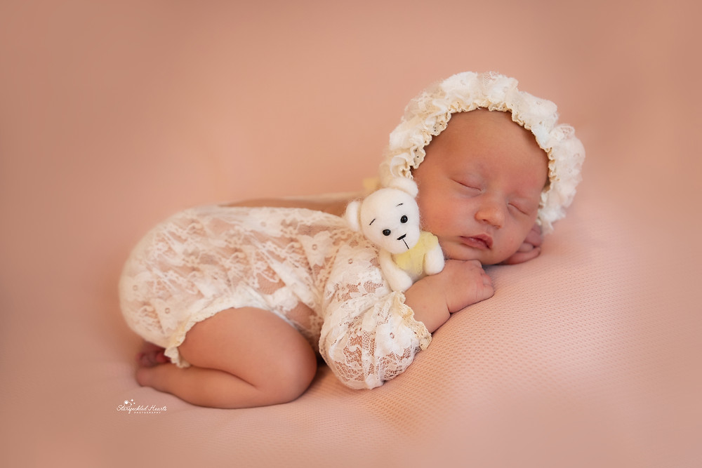 baby girl wearing a lace romper and bonnet set lying on a pink backdrop cuddling a white teddy