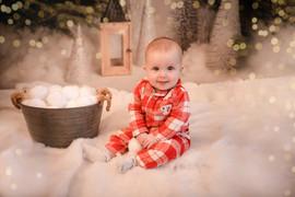 adorable baby girl wearing christmas pyjamas sitting on a snowy floor smiling