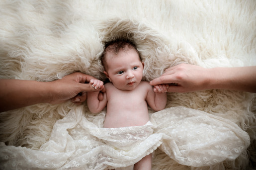 newborn baby girl lying on a white furry rug, holding her parents hands for her newborn photography session with starspeckled hearts photography near berkshire