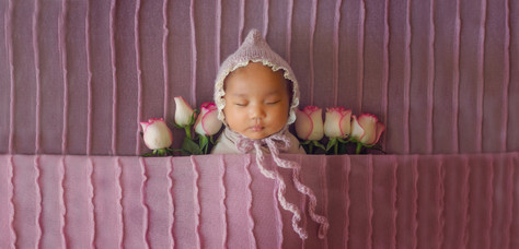 beautiful newborn girl wearing a pink knitted bonnet, laying among white and pink roses
