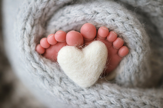 newborn photography of ten tiny baby toes curled around a small white felted heart, feet wrapped in a grey knitted wrap