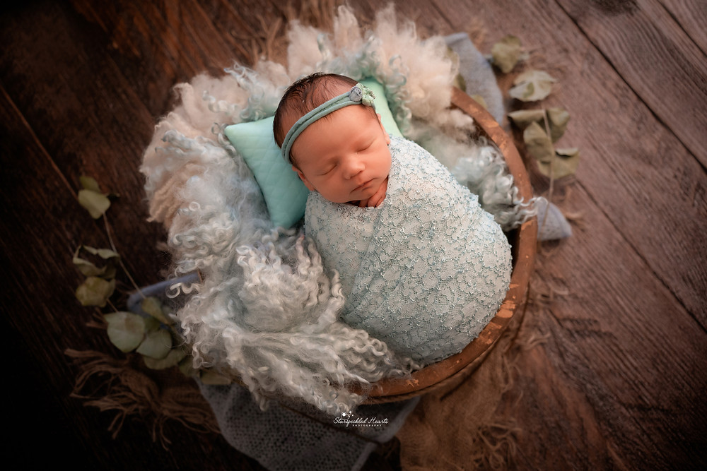 adorable sleeping newborn baby wrapped in a floral wrap lying in a basket on dark brown wooden floor