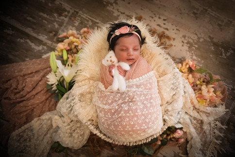 gorgeous baby girl wearing white lace wrap and floral headband, lying in a bowl surrounded by pink flowers