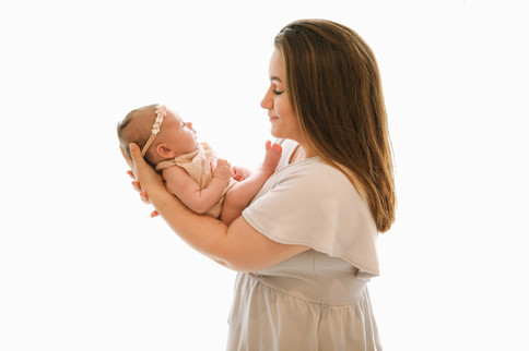 brown haired woman holding up her newborn daughter in her arms, both wearing all white