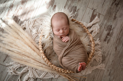 adorable sleeping newborn baby boy wrapped in brown for his newborn session with starspeckled hearts photography