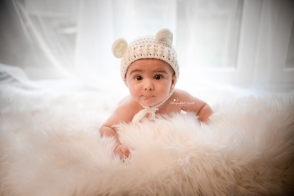 baby boy wearing a white knitted bear bonnet, lying on a white fluffy rug