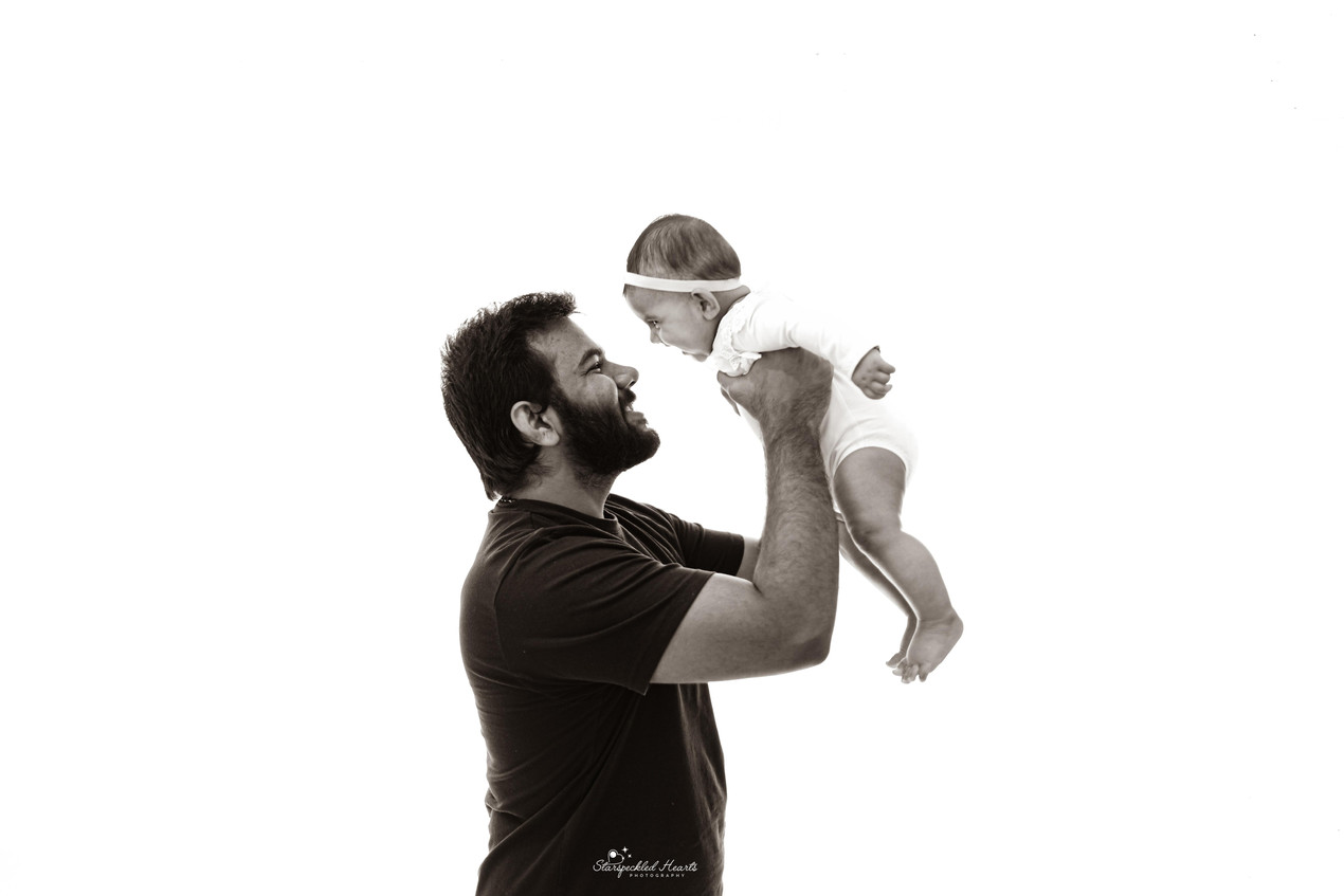 father holding up his daughter in his hands