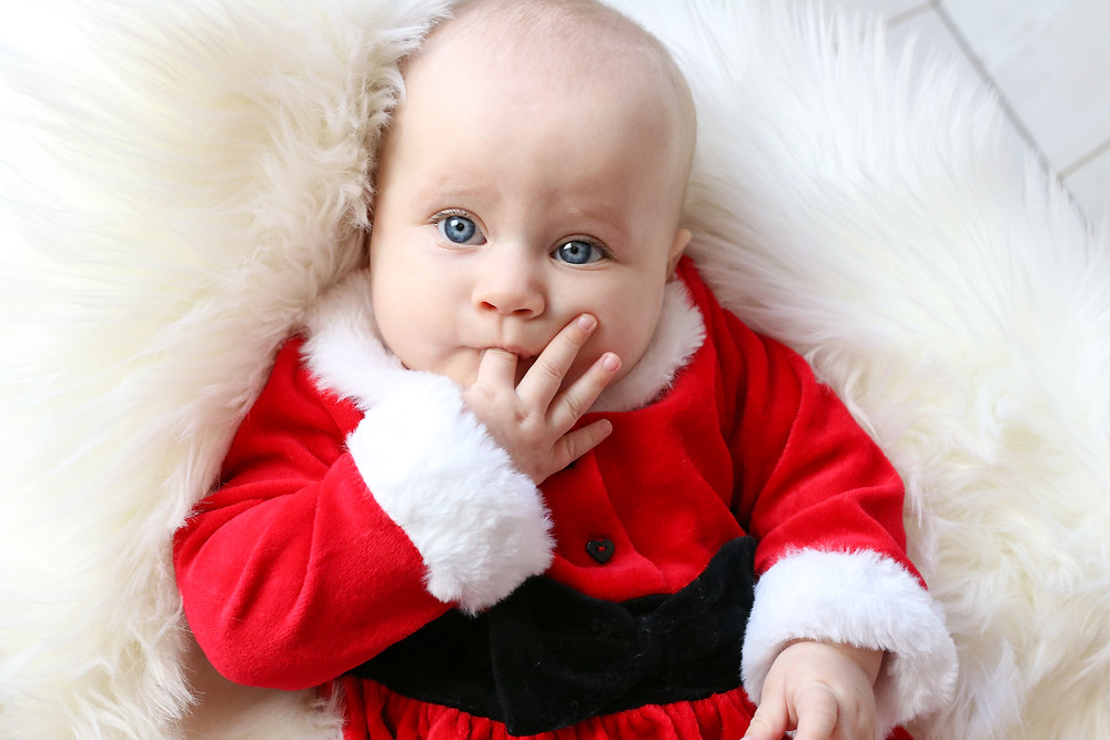 cute baby girl with big blue eyes wearing santa claus outfit