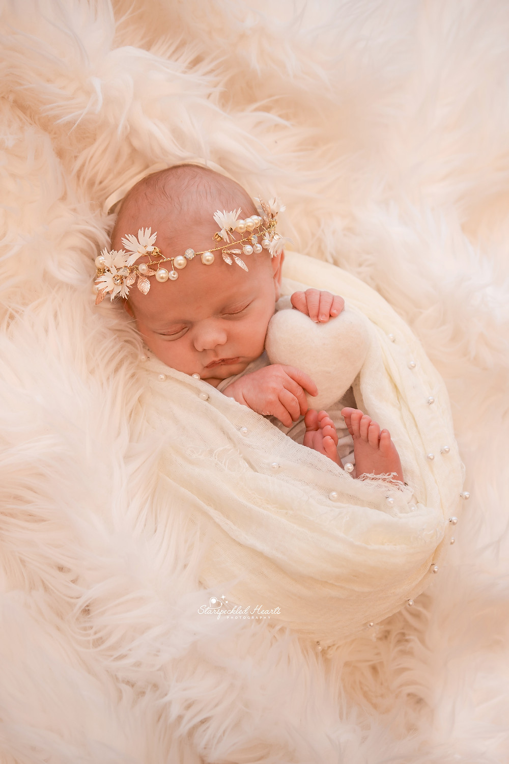 newborn girl wrapped in a white pearl wrap wearing a matching pearl tiara