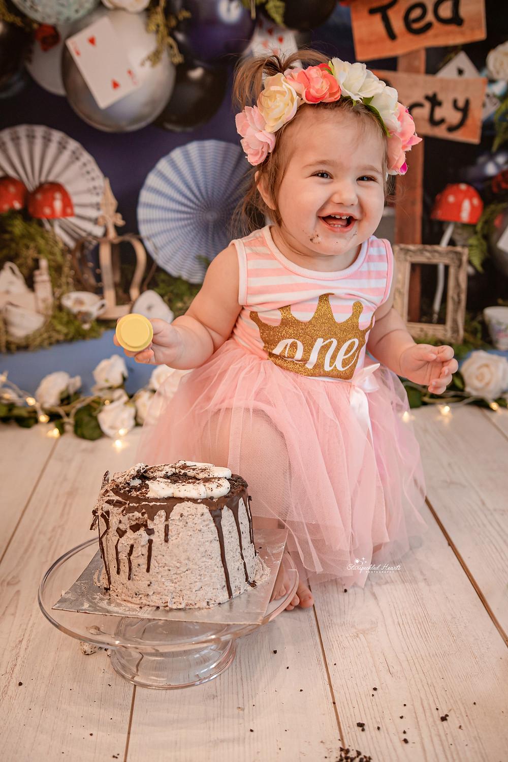 baby girl wearing a pink tutu sitting next to a cake
