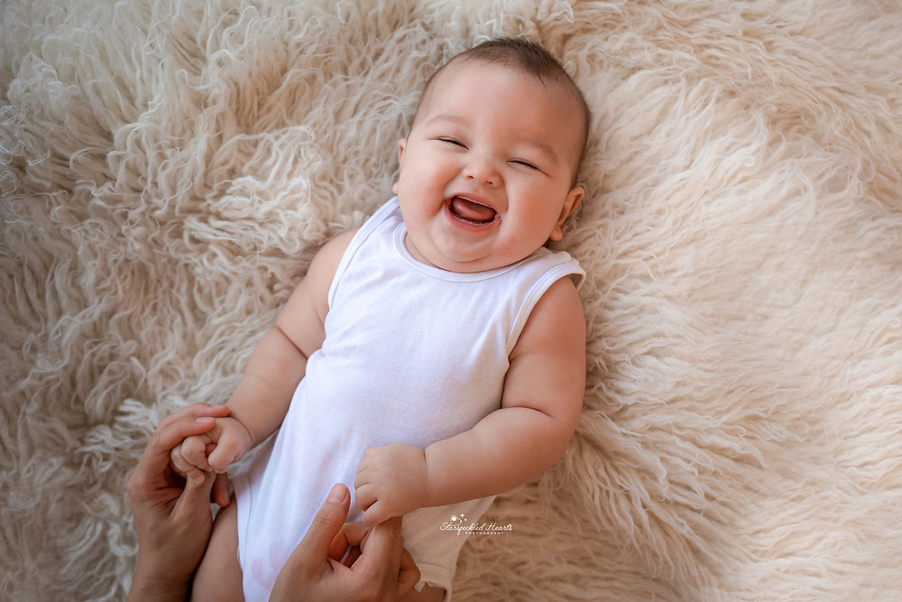 gorgeous baby boy smiling lying on a white rug