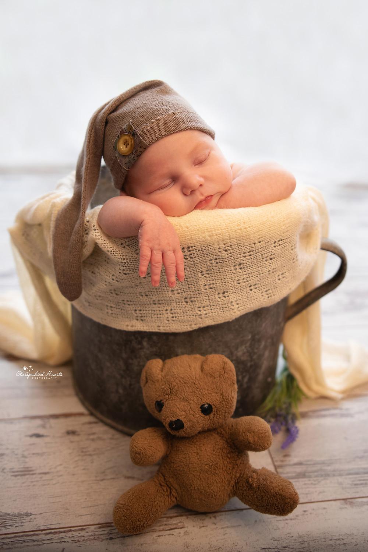 sleeping newborn wearing a brown sleepy cap, head on hands in a bucket